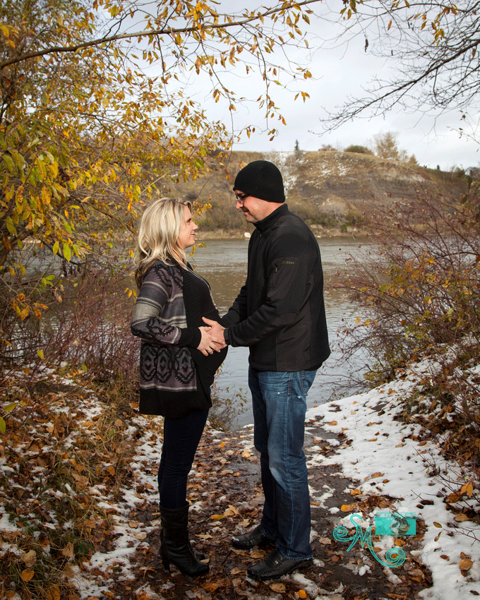 a couple stand face to face holding her pregnant belly in front of a river and among fall leaves
