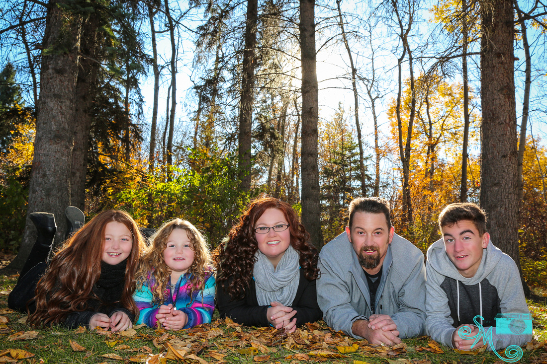 a mom, dad and three children lay on stomachs on the leaves at Hawrelak park