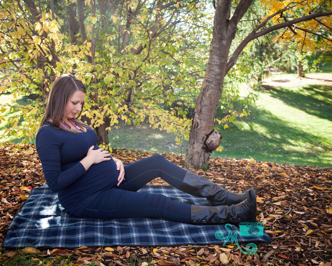 a pregnant lady sits on a blanket amid fall leaves