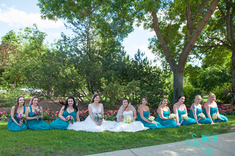 two brides and all their bridesmaids with the same colour dresses