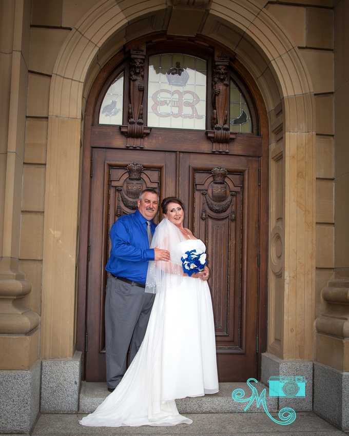 bride and groom pose in doorway of Alberta Legislative building
