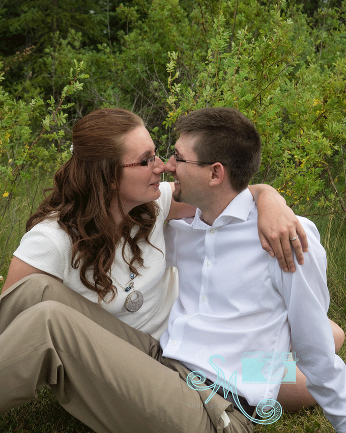 man and woman sitting in grass touching noses