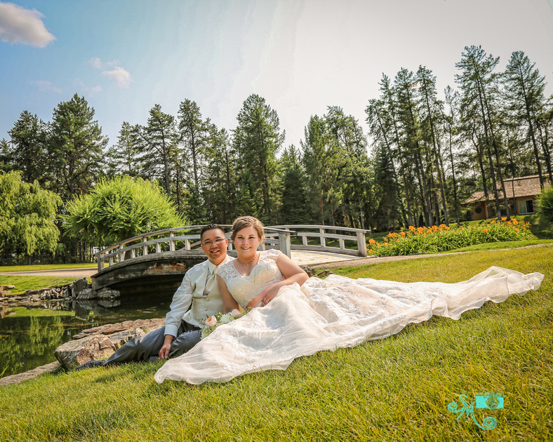the bride and groom sit on the grass with the bridge at the Japanese Gardens in the background