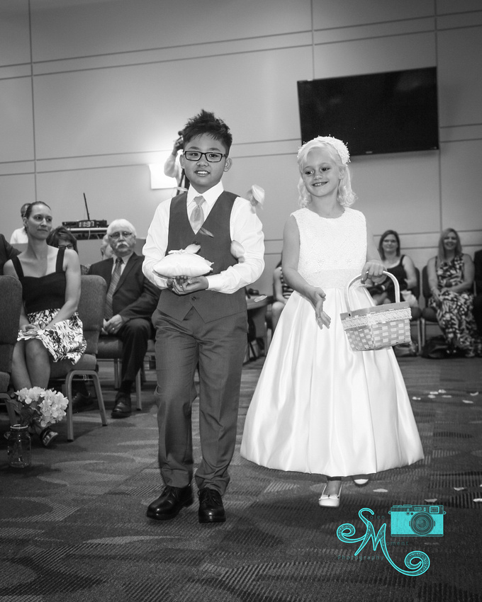 a ring bearer and flower girl walk down the aisle