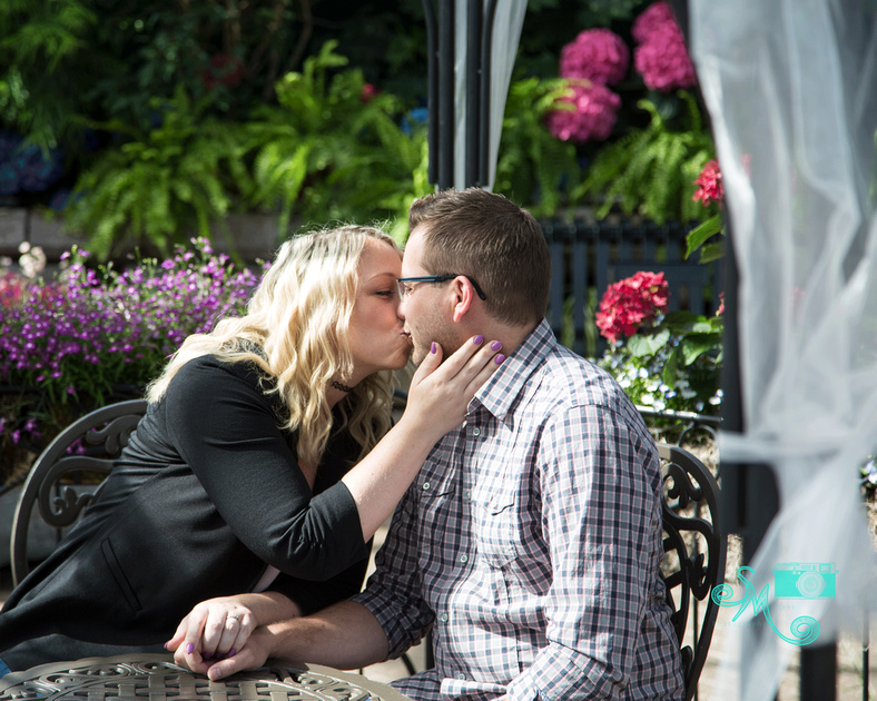 a woman leans in to kiss her fiance while sitting at a table